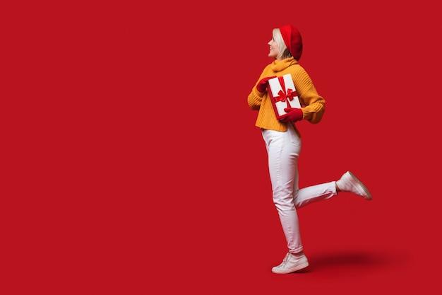 Mulher adorável com chapéu e luvas vermelhas posando em uma parede com espaço livre segurando uma caixa de presentes e sorrindo