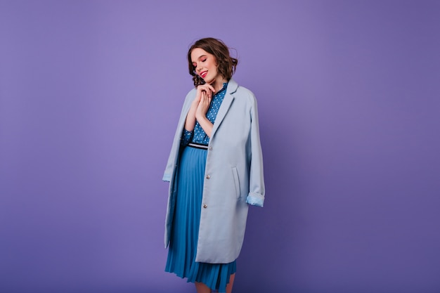 Mulher adorável com maquiagem da moda, olhando para baixo durante a sessão de fotos. menina alegre e encaracolada com casaco azul.