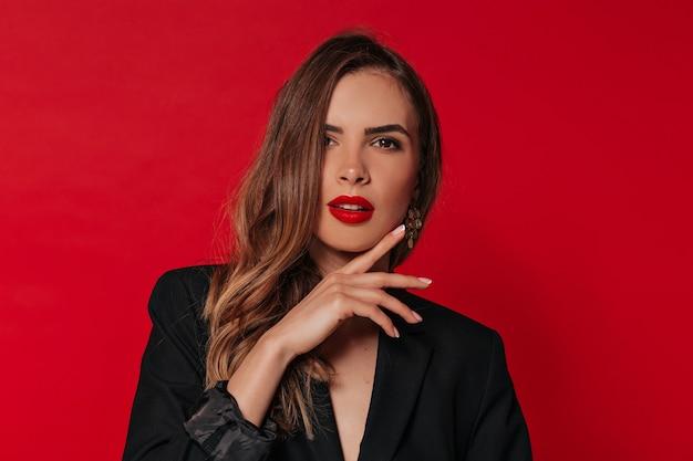 Mulher adorável com maquiagem de noite posando sobre uma parede vermelha, tocando seu rosto