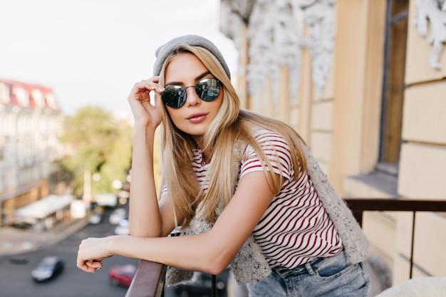 Mulher adorável com pele clara posando de óculos escuros enquanto relaxa na varanda