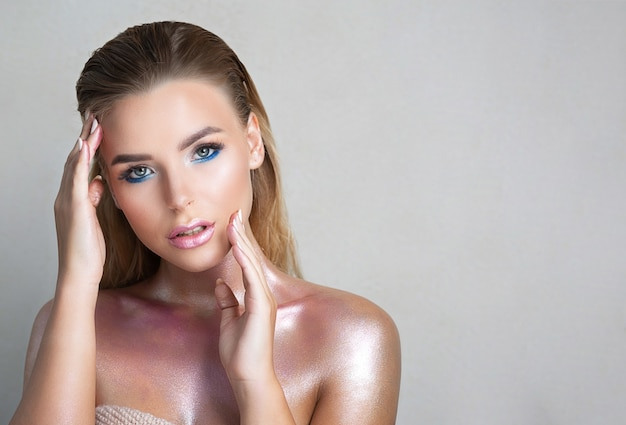 Mulher adorável com pele impecável e brilho metálico no pescoço e ombros