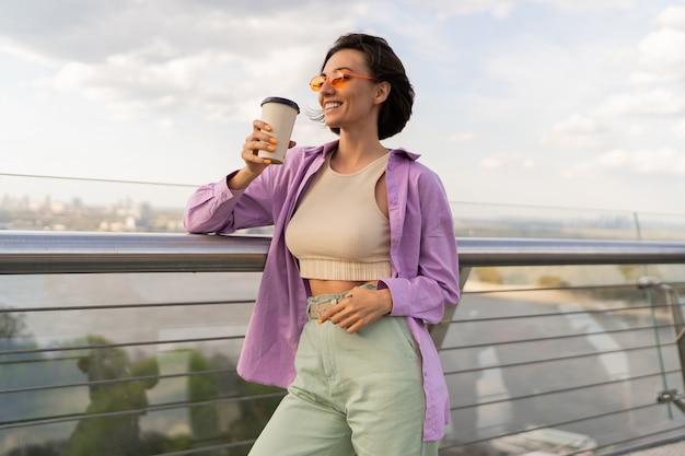Mulher adorável com penteado curto caminhando na ponte moderna em um dia ventoso de verão