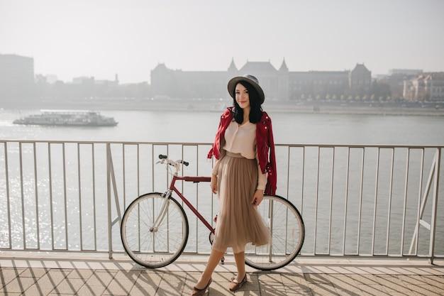 Mulher adorável com saia bege em pé perto de uma bicicleta
