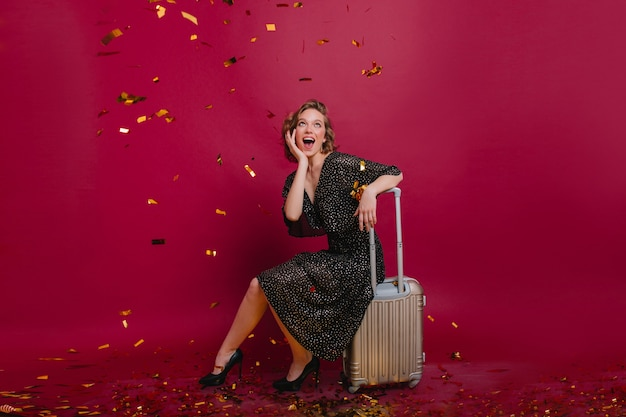 Mulher adorável com sapatos elegantes olhando confete com espanto