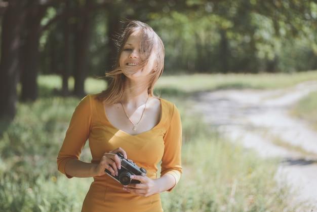 Mulher adorável com uma câmera fotográfica