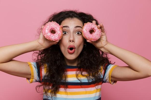 Mulher adorável de 20 anos com cabelo encaracolado se divertindo e segurando rosquinhas isoladas em rosa