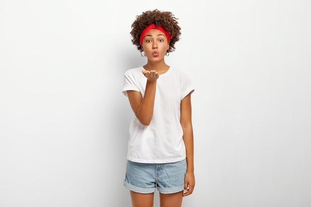 Mulher adorável de aparência agradável com corte de cabelo afro, franze os lábios e sopra beijo no ar, tem expressão sedutora