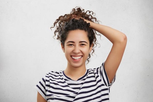 Mulher adorável de aparência agradável e expressão feliz, pega os cabelos cacheados no rabo de cavalo, se diverte,