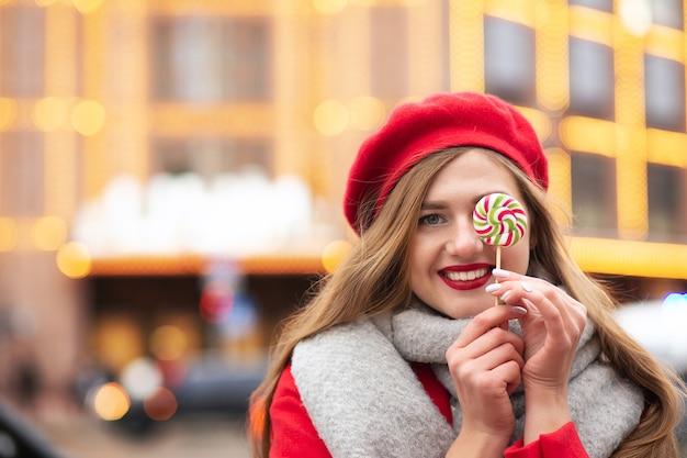 Mulher adorável e alegre vestida com um casaco vermelho e um lenço quente segurando um doce de caramelo na rua no inverno