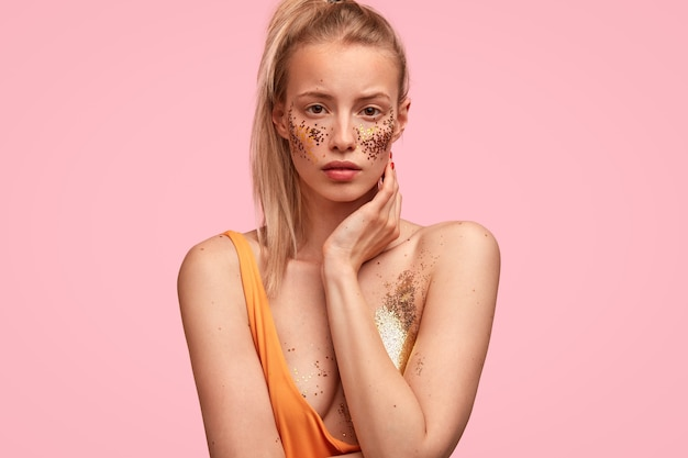 Mulher adorável e autoconfiante tem maquiagem festiva, parece sério, se prepara para uma festa com amigos, tem ombros nus,