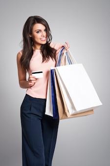 Mulher adorável e elegante com cartão de crédito e sacolas de compras