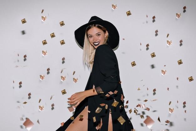 Mulher adorável e encantadora com cabelos loiros usando roupas elegantes, dançando e se divertindo sob confete