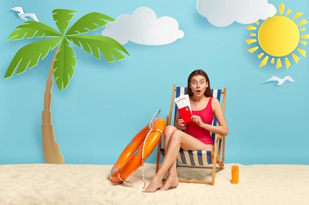 Mulher adorável e envergonhada segurando bilhetes de avião com passaporte, posa em cadeira de praia, faz boa viagem no mar, vestida de maiô