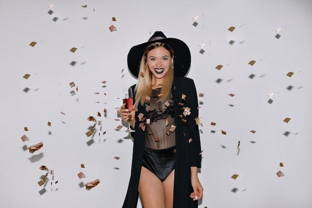 Mulher adorável e feliz com cabelo loiro posando com vinho na parede isolada com confete