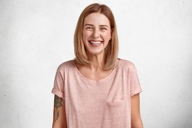 Mulher adorável e feliz com um sorriso largo e cheio de dentes brancos, usa uma camiseta casual grande demais, tem uma tatuagem, um visual simpático atraente