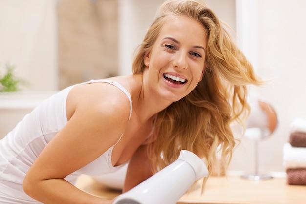Mulher adorável e feliz secando cabelo no banheiro