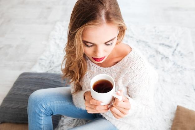 Mulher adorável e fofa com cabelo comprido e batom vermelho segurando uma xícara de chá dentro de casa