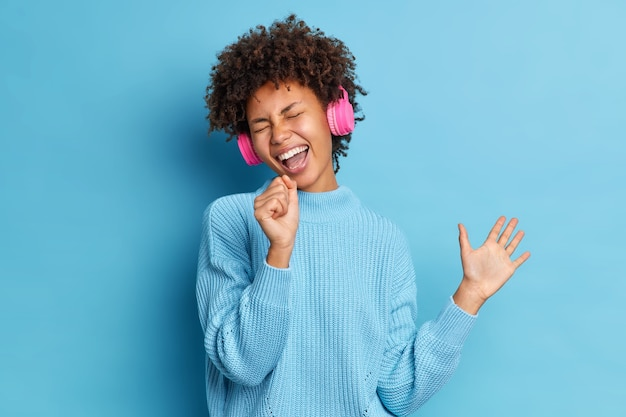 Mulher adorável e otimista tem cabelo encaracolado ouve música em fones de ouvido sem fio, canta junto levanta as mãos usa um suéter casual empolgado com a música favorita vestida casualmente