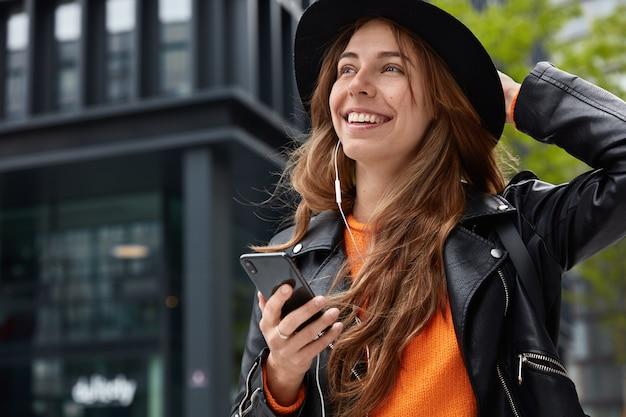 Mulher adorável e sonhadora tocando um chapéu estiloso, caminhando em um cenário de urabn e usando um dispositivo moderno