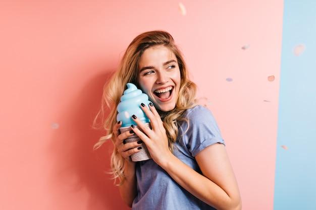 Mulher adorável e sorridente segurando um grande sorvete