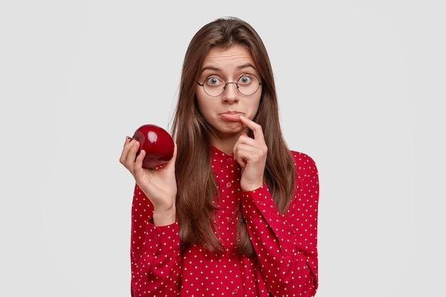 Mulher adorável e triste vegeteriana segura maçã vermelha fresca, franze o lábio inferior, mantém uma dieta saudável, come frutas, tem cabelo longo e liso, vestida com blusa de polca