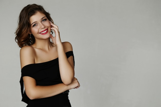 Mulher adorável elegante posando com vestido preto