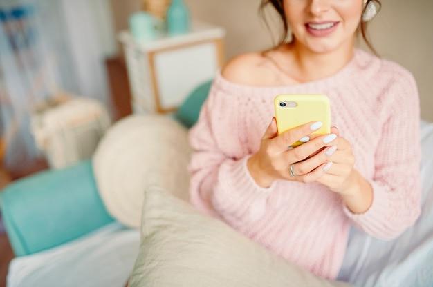 Mulher adorável em um ambiente doméstico acolhedor olha para o telefone