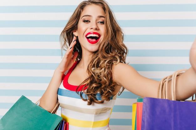 Mulher adorável encaracolada expressando emoção durante as compras. menina sorridente e entusiasmada com lábios vermelhos, posando com compras.
