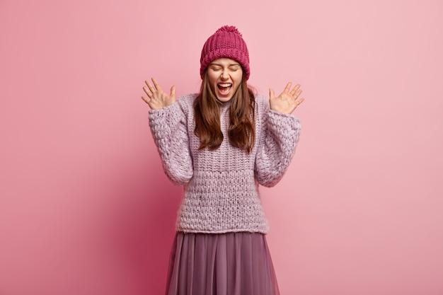 Mulher adorável exultante de expressão alegre, grita de alegria e emoção, levanta as palmas das mãos, sendo muito emotiva usa chapéu com pompon, suéter tricotado e saia plissada. reação em algo agradável
