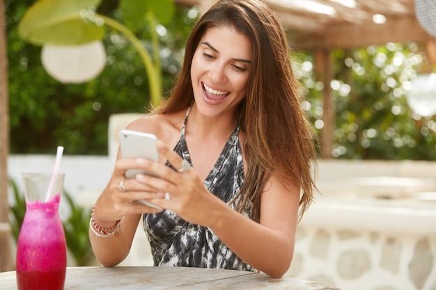 Mulher adorável feliz com cabelo comprido escuro, faz download da publicação no blog do smartphone, descansa em um café na calçada do resort