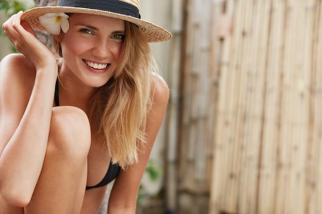 Mulher adorável feliz com chapéu de palha e maiô, se sente satisfeita com um bom descanso de verão
