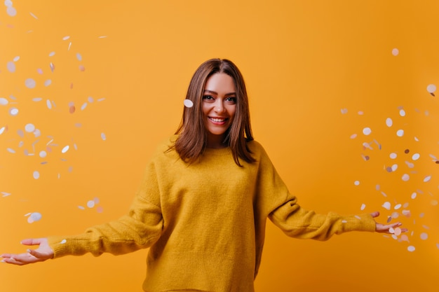 Mulher adorável feliz no suéter amarelo rindo na parede brilhante. retrato interior de atraente garota posando com confete.