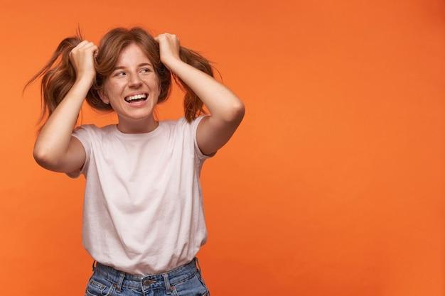 Mulher adorável jovem feliz com cabelo ruivo em uso casual, olhando para o lado com um largo sorriso e segurando as caudas