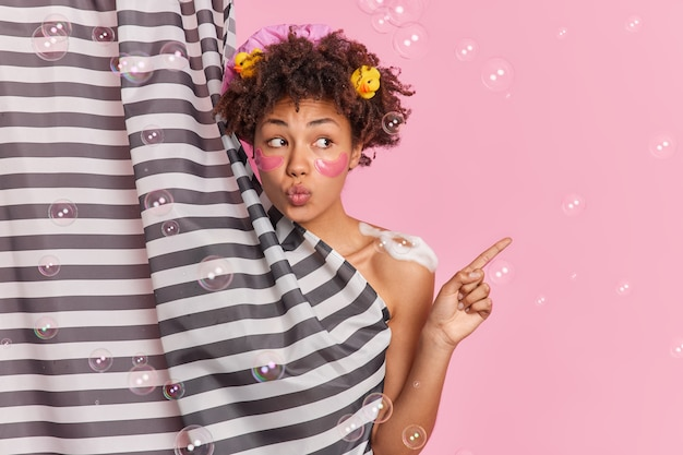 Mulher adorável mantém os lábios dobrados, toma banho matinal no banheiro realiza rotina de autocuidado aplica adesivos de colágeno sob os olhos, poses atrás da cortina