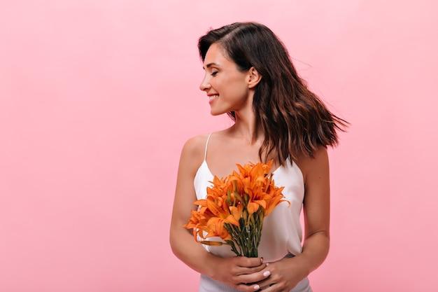 Mulher adorável no topo, risos e poses com ramo de flores em fundo rosa
