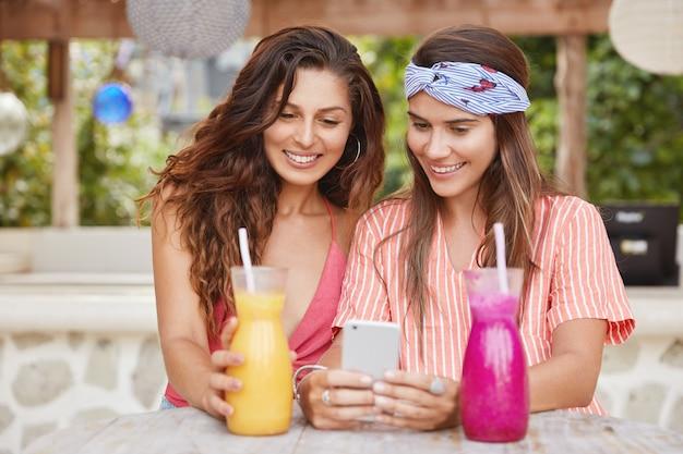 Mulher adorável positiva e sua melhor amiga seguram um celular moderno, lêem boas notícias na internet ou veem fotos nas redes sociais