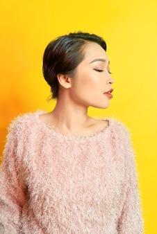 Mulher adorável que expressa emoções positivas verdadeiras durante a sessão de fotos com um casaco de pele rosa. retrato interno da garota glamourosa ativa em pose confiante e sorrindo.