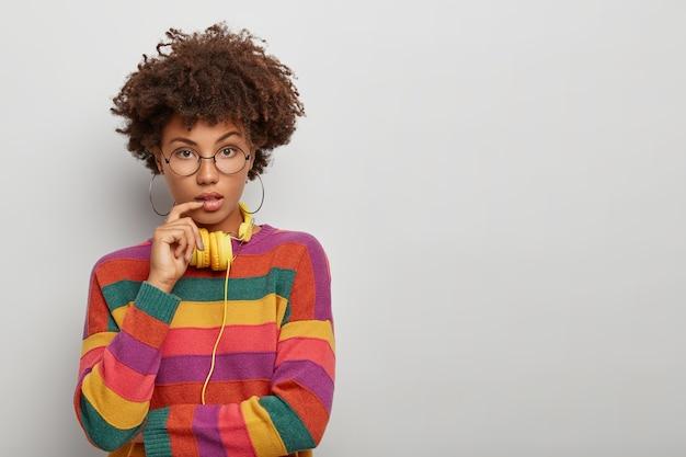 Mulher adorável segura de si com cabelos cacheados naturais, mantém o dedo perto dos lábios, usa brincos redondos, óculos e macacão listrado, modelos contra parede branca