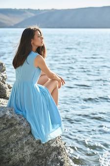 Mulher adorável sentada na pedra perto do rio dniester