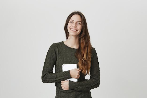 Mulher adorável sorridente abraçando tablet digital, trabalhando freelance