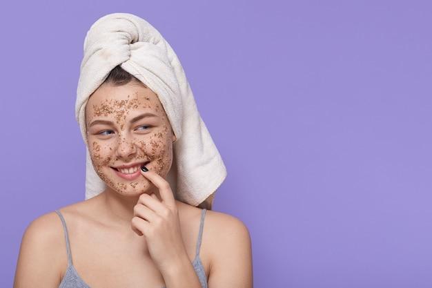 Mulher adorável sorridente posando com máscara cosmética isolada em lilás, olhando para o lado com expressão facial de flerte