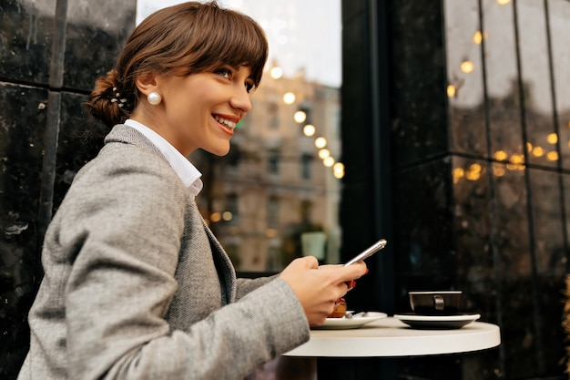 Mulher adorável sorridente vestindo uma jaqueta cinza sentada em um café ao ar livre está usando o smartphone e esperando o encontro no fundo das luzes da cidade. foto de alta qualidade