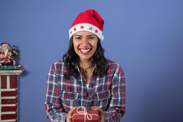 Mulher adorável sorrindo enquanto segura um pequeno presente de natal