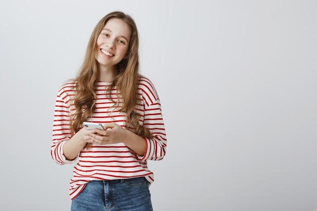 Mulher adorável sorrindo feliz e usando smartphone
