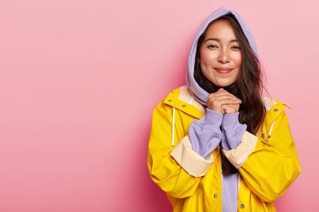 Mulher adorável tocada com aparência agradável, mantém as mãos juntas ao ser tocada por algo, usa casaco com capuz e capa de chuva