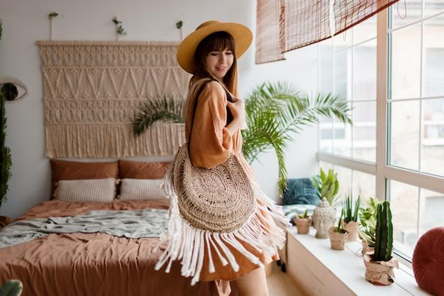 Mulher adorável vestido de linho e chapéu de palha posando no apartamento de estilo boho