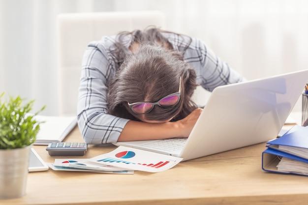 Mulher adormeceu em sua mesa de trabalho com gráficos de negócios e um caderno na frente dela.