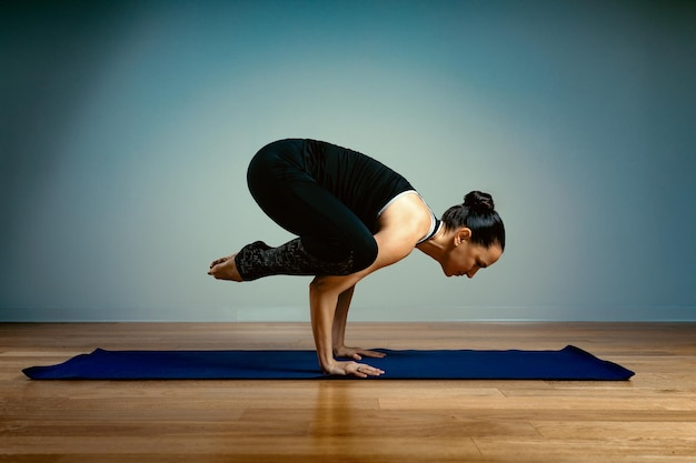 Mulher adulta, 45-55 anos de idade em boa forma, fazendo ioga, posando em um fundo azul do estúdio, com um piso de madeira sobre uma esteira de treinamento. ioga, alongamento, estilo de vida saudável.