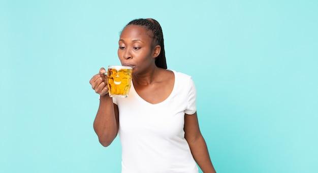Mulher adulta afro-americana segurando um copo de cerveja