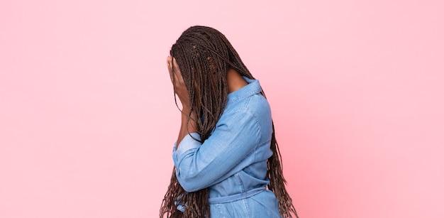 Mulher adulta afro-negra cobrindo os olhos com as mãos com um olhar triste e frustrado de desespero, chorando, vista lateral